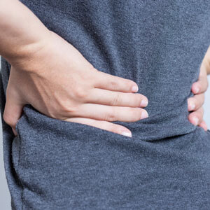 woman-in-gray-shirt-holding-lower-back-sq-300