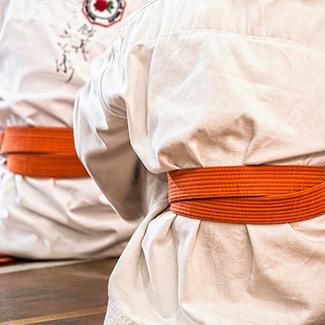 people sitting in karate uniforms