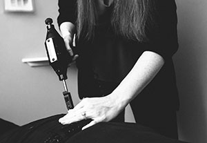 Doctor using a chiropractic instrument on patient
