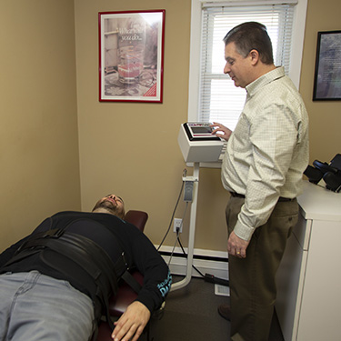 Man on spinal decompression table doctor onlooking