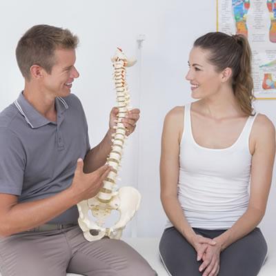 Chiropractor holding model spine