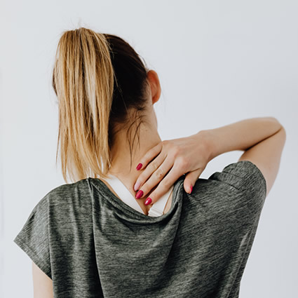 woman reaching her back neck