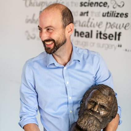 Doc smiling with sculpture