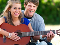 woman and man playing guitar