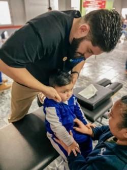 Dr. Alex Morrow adjusting a child