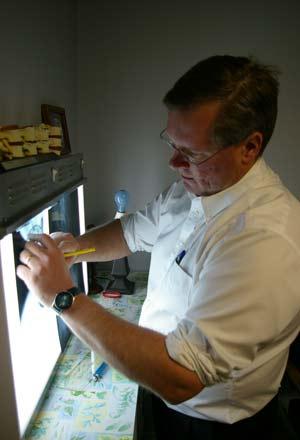 Dr. Wood, Arkansas City Chiropractor, studies a patient's x-rays