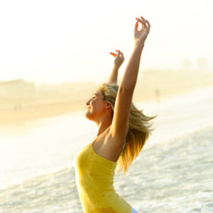 Lady on beach with hands in air