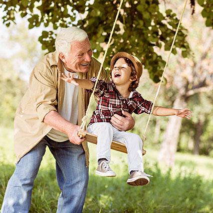 Older man pushing child on swing