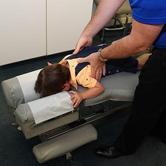 Dr. Alex adjusting little boy