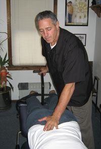 Dr Karas of Chiropractic Health Center of Hamburg using the Flexion Distraction Chiropractic Technique to adjust a patient.