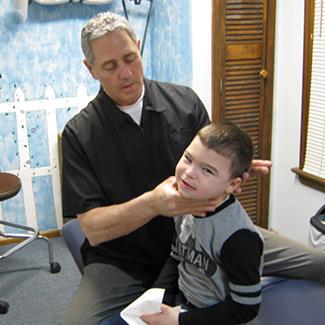 Dr. Karas adjusting a child patient