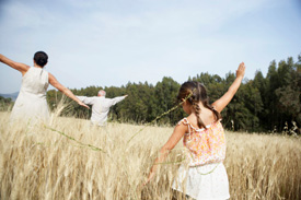 Family doing aeroplanes in field