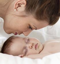 mom kissing baby sleeping