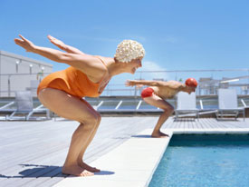 Older couple diving into pool