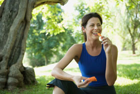 woman in the park smiling and eating carrots
