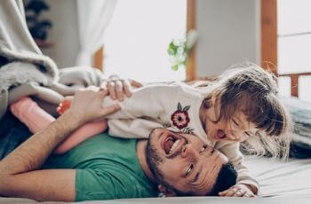 Dad and daughter laughing.