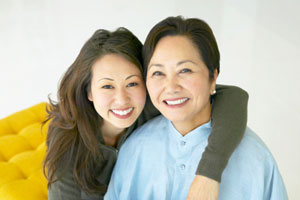 Adult daughter with arm around her mom