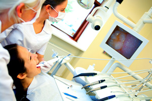 Dentist using an intra-oral camera to view a patients teeth