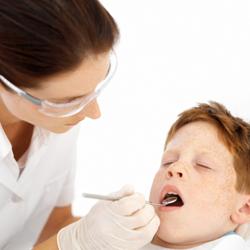 A dentist examining a little boy's teeth