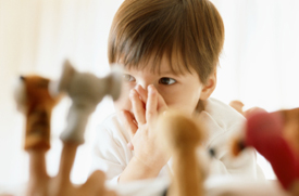 Boy with hand over his mouth looking at finger puppets
