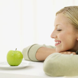 Smiling woman looking at an apple