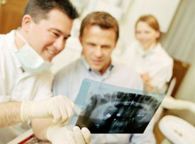 Dentist and patient reviewing x-rays