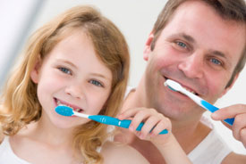 Father and daughter brushing together