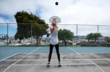 Woman shooting basketball.