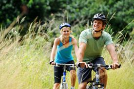 Couple biking thru a field