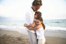 Children hugging man on beach
