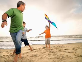 Oshawa man and children running on beach.