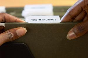 Woman flipping through health insurance file folder
