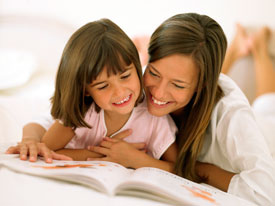 Woman and little girl looking at a book.