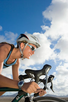 woman ridding bicycle with blue sky