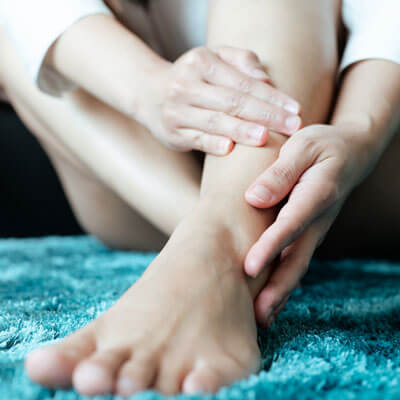woman holding ankle and leg in pain
