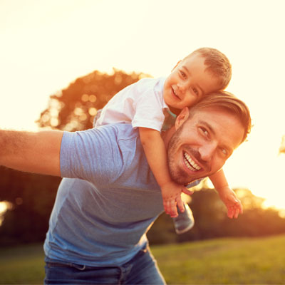 father smiling and playing with son at the park