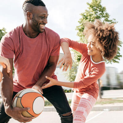 Dad and daughter playing basketball