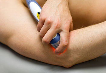 Doctor using laser therapy on elbow