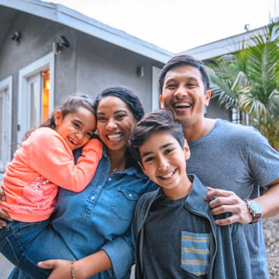 family smiling in front of house
