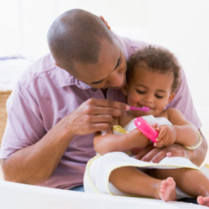 Dad brushing child's teeth