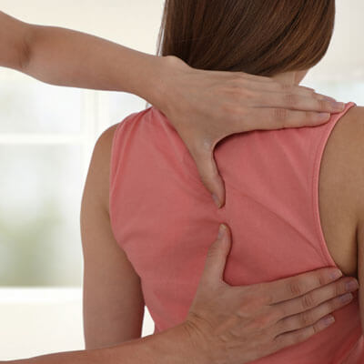 Chiropractor with hands on womans back
