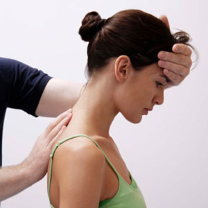 Woman having her upper spine adjusted while standing up
