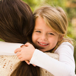 Young daughter hugging her mom