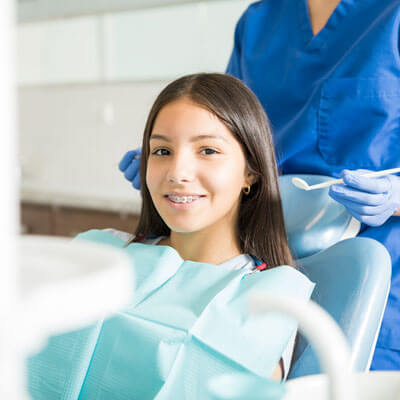 Girl with braces in dental chair