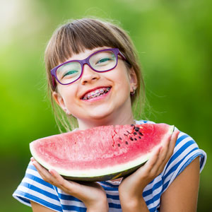 young girl with orthodontics holding watermelon