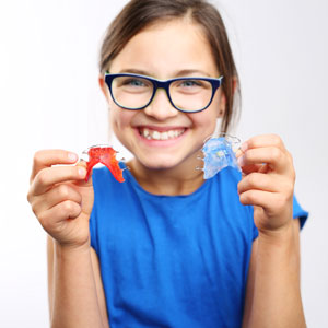Young girl holding retainers