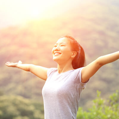 woman smiling arms out standing on mountain