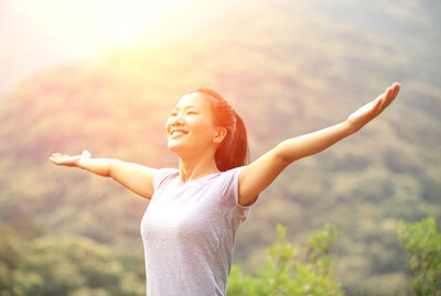 Happy woman with arms out in the mountains