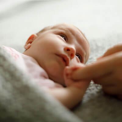 Newborn holding moms finger