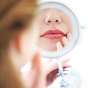 Woman looking in hand mirror at her face